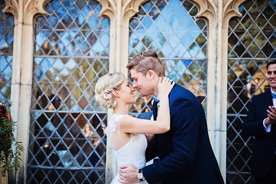 A couple kissing with rustic window at the backdrop at Montsalvat
