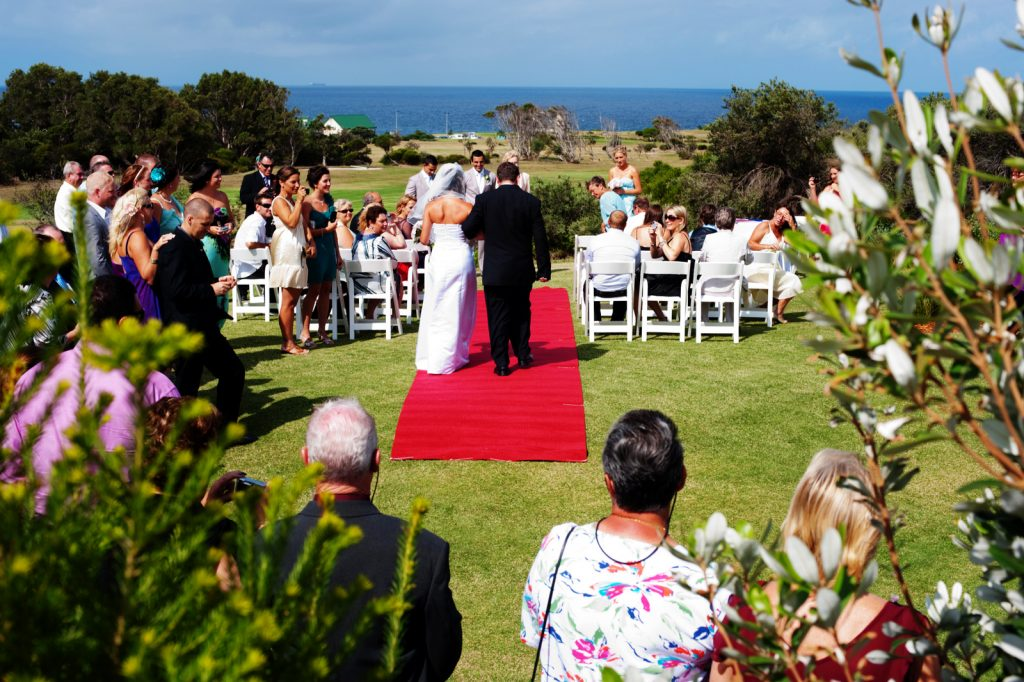 A couple approaching the altar with ocean as the backdrop