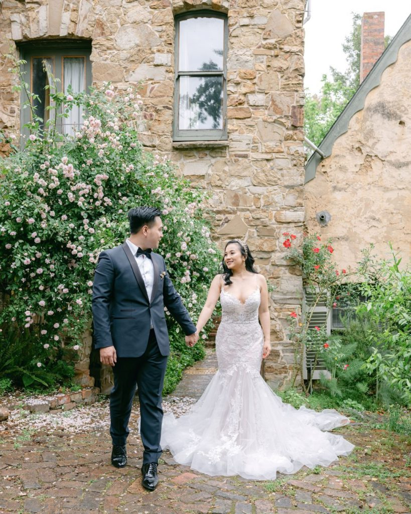 A couple is holding hand in the garden of Montsalvat