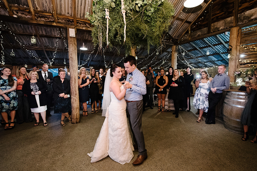 A wedding couple is dancing in the middle of a barn surrounded by the guests