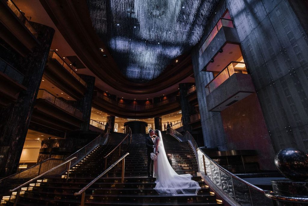 A wedding couple standing on the elegant staircase of Crown Melbourne