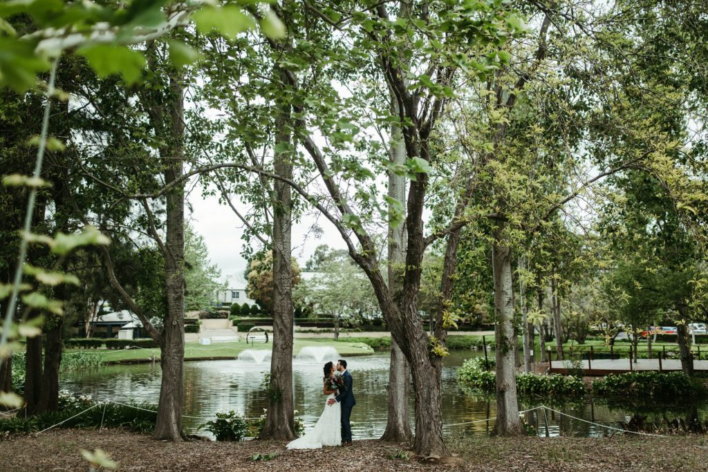 A couple standing on the lakeside under shaded trees