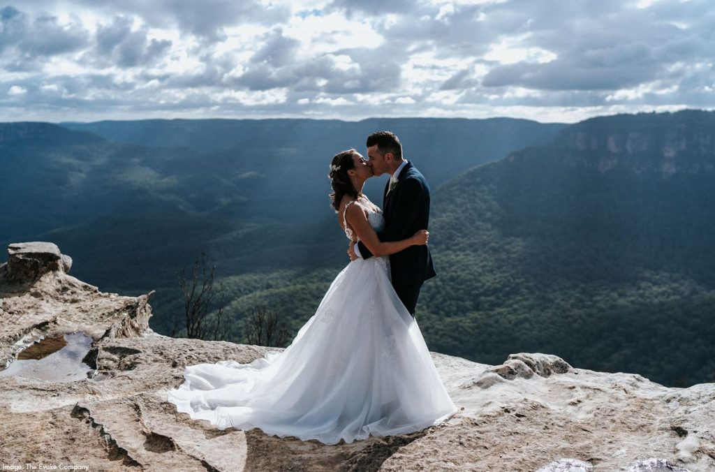 A couple is kissing with Blue Mountains view as a backdrop
