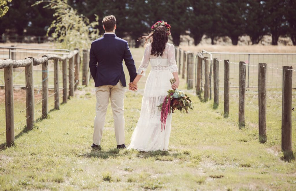 A wedding couple holding hands at Hedge Farm picture is taken from the back