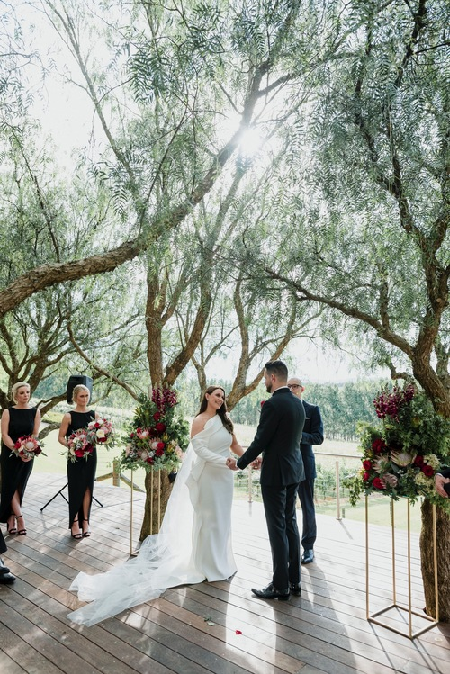 A couple is exchanging a vow under shady trees at TarraWarra Estate