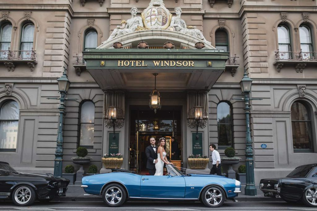A wedding couple in front of The Hotel Windsor