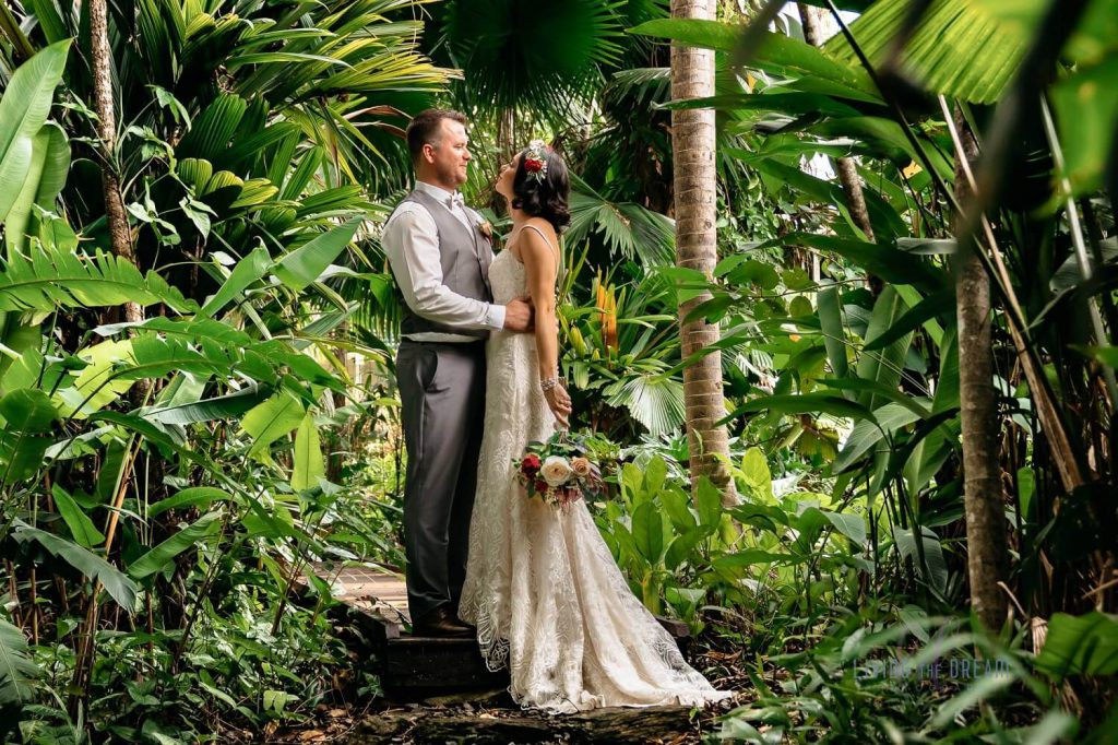 A wedding couple is looking into each other's eyes at a garden