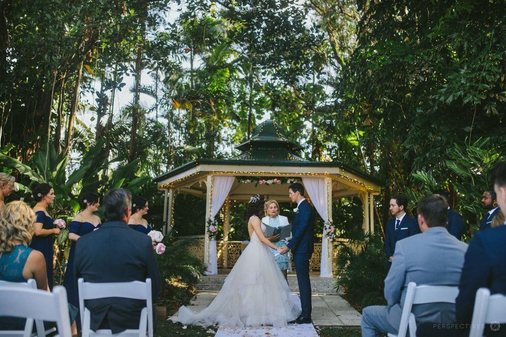 A wedding vow exchange with garden gazebo as the backdrop