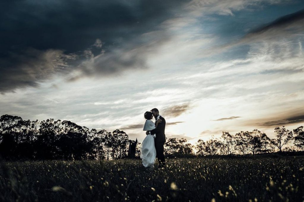 A wedding couple facing each other amid a bushland