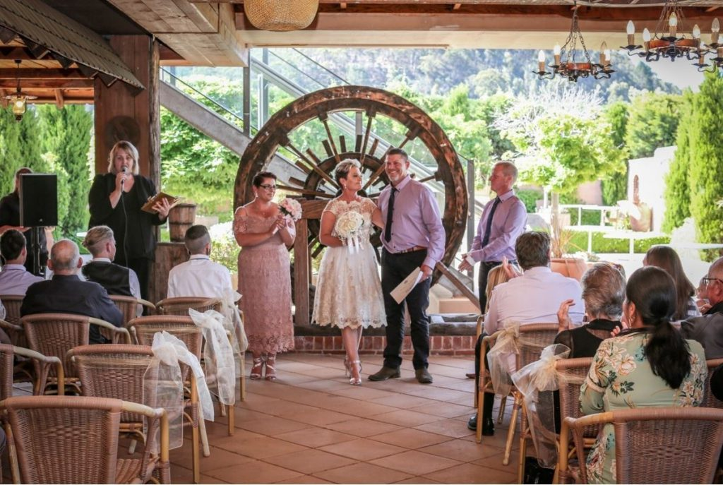 A couple standing in front of the wedding guests at Lithgow Workies