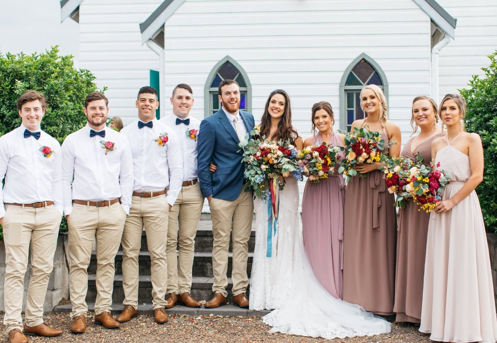 Wedding couple, bridesmaids, and groomsmen in front of the chapel
