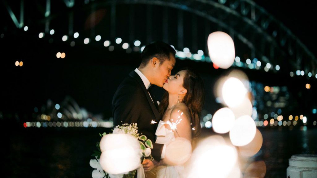 A wedding couple kissing with Sydney bridge as the backdrop