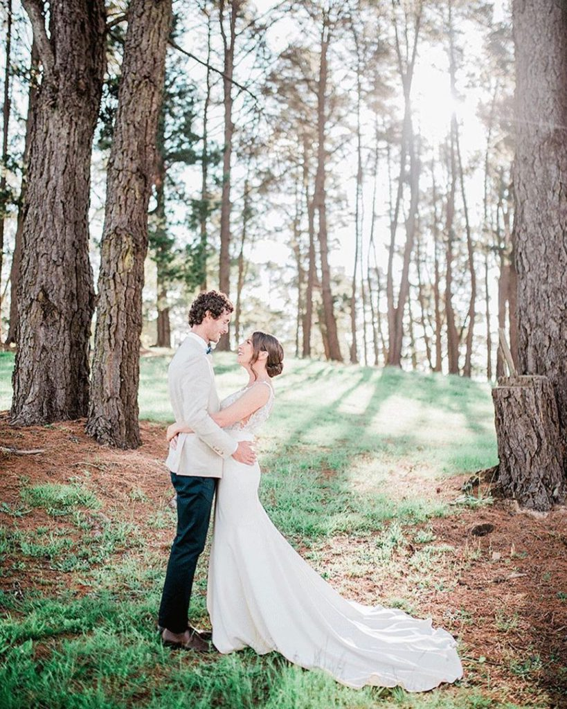 A wedding couple is facing each other under towering trees