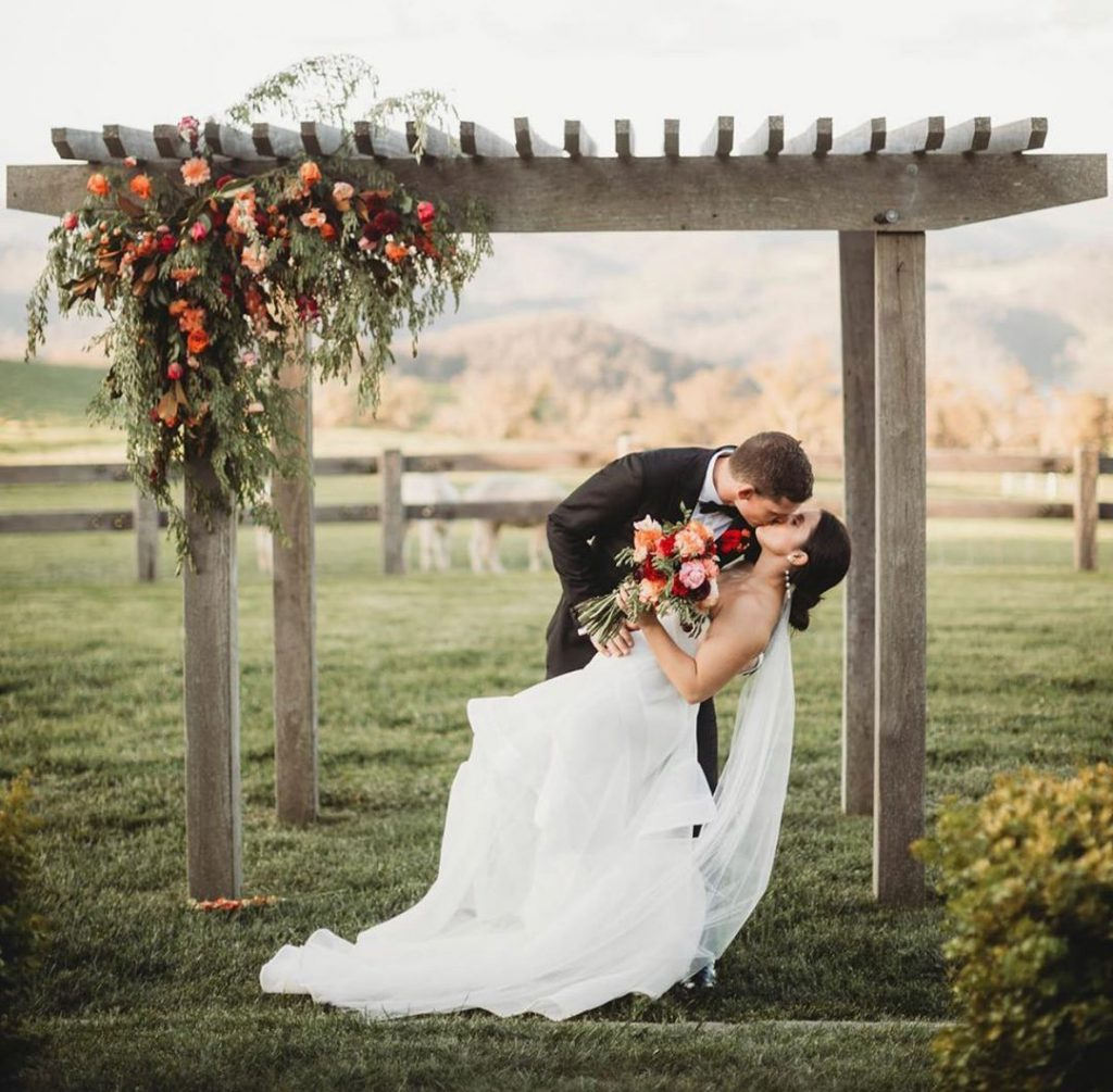 A wedding couple is kissing under a wooden arbour