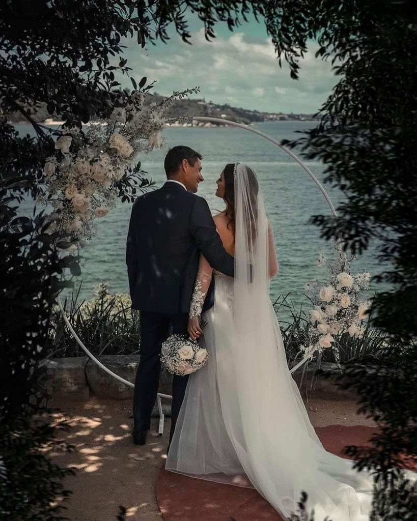 A wedding couple looking at each other in front of waters