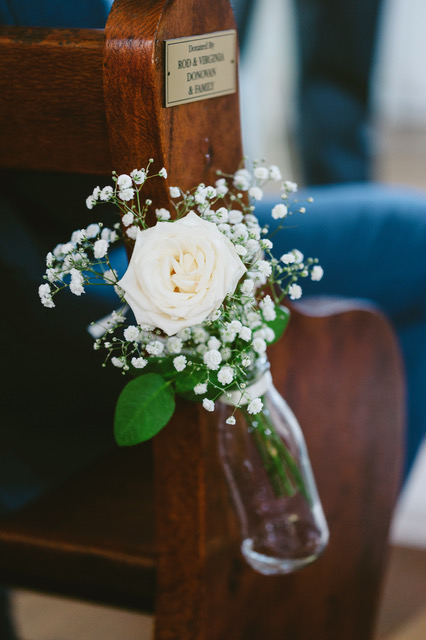 White rose and bany breath put in glass bottle and tied to wooden chair
