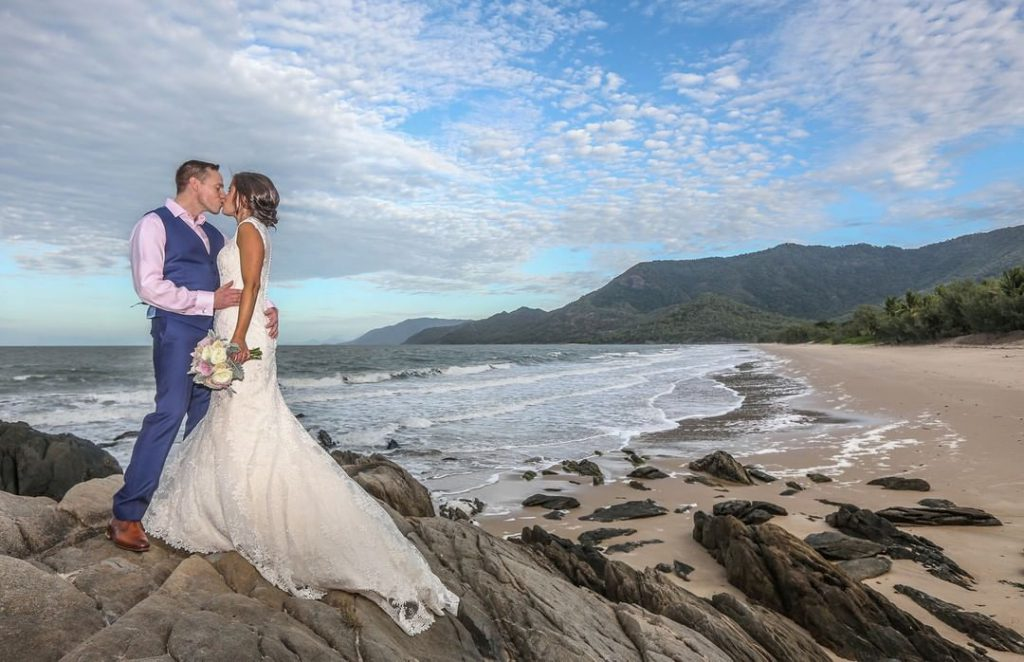 A wedding couple is kissing at the beach