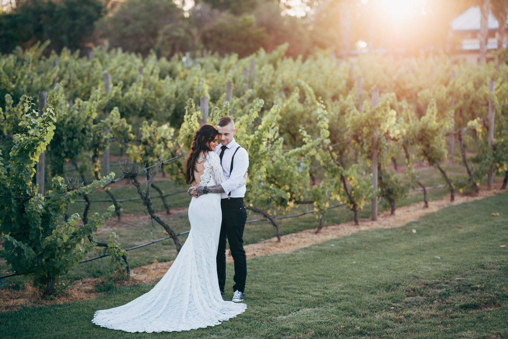 A wedding couple hugging with vineyards at the background