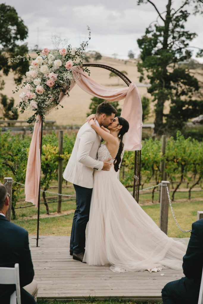 A couple is kissing with vineyards as the backdrop