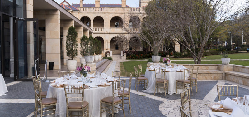 A terrace with round tables and gold tiffany chairs for a wedding