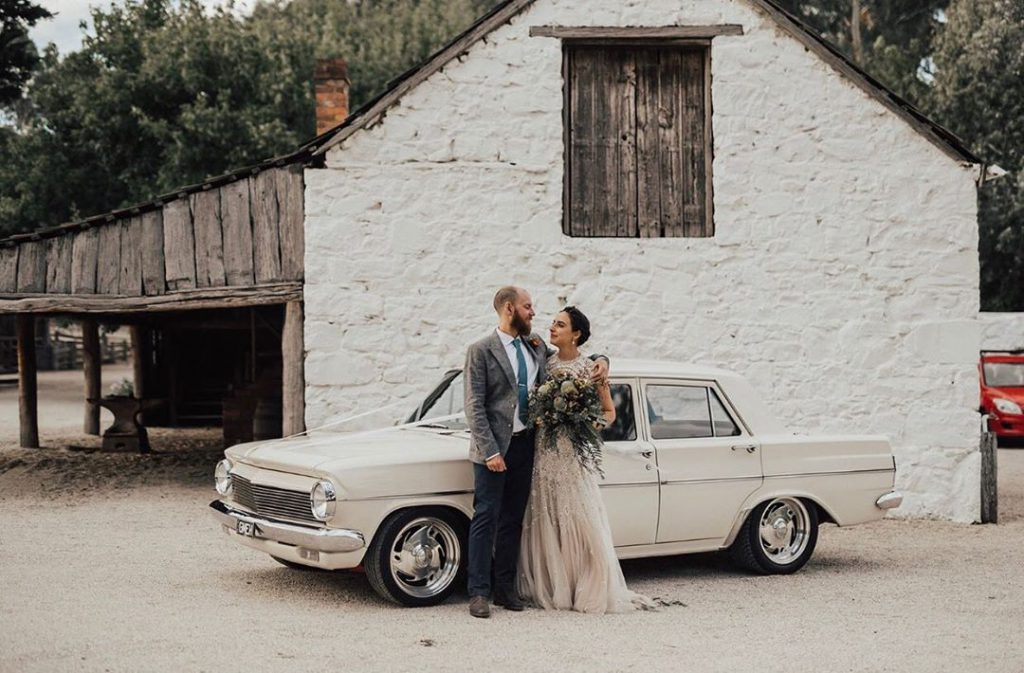 A couple wit the background of a white vintage car and homestead at Emu Bottom Homestead