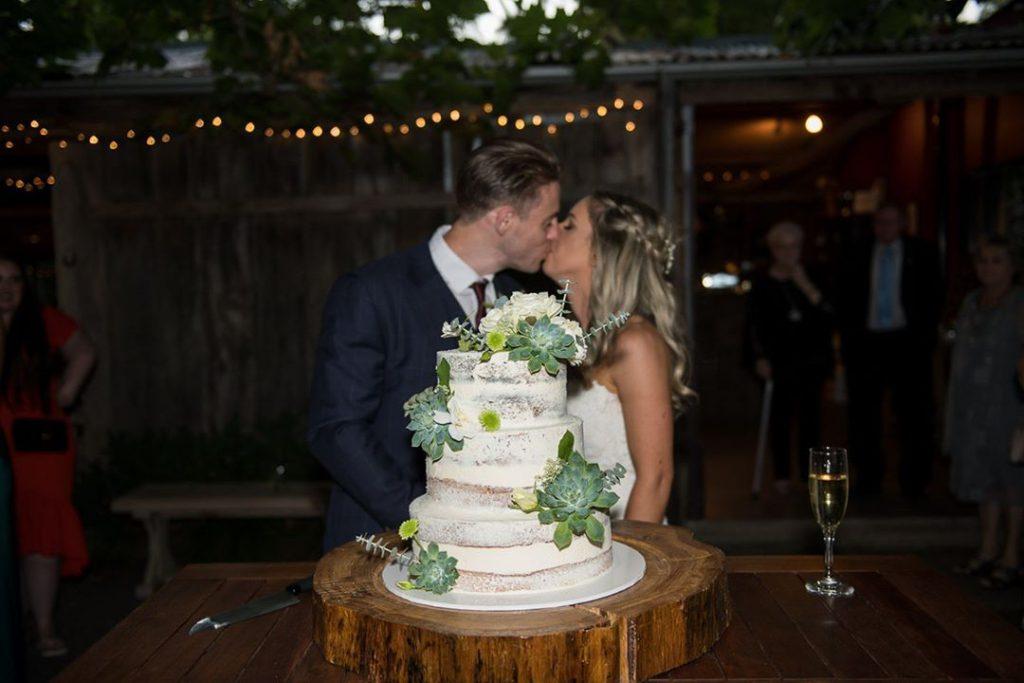 A wedding couple kissing neare wedding cake