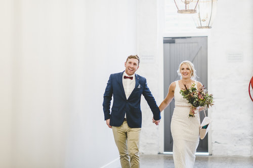 A wedding couple is holding hand, walking in a white room