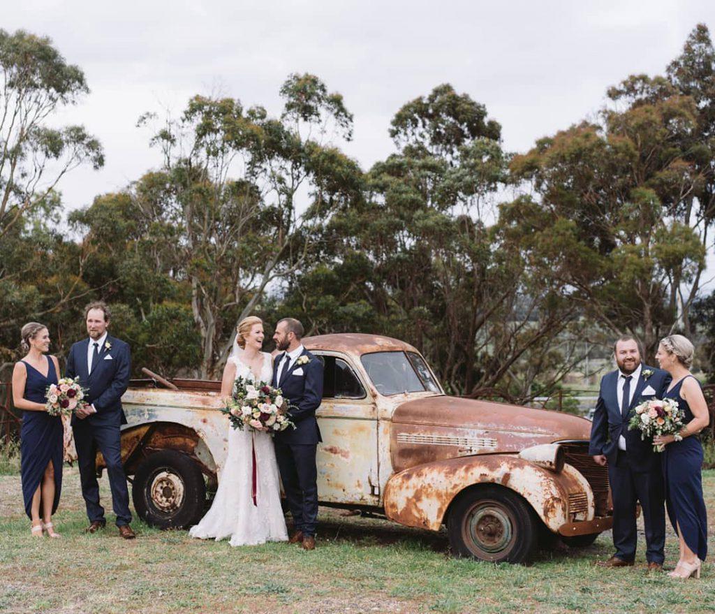 A wedding couple, bridesmaids, and groomsmen posing near a used car