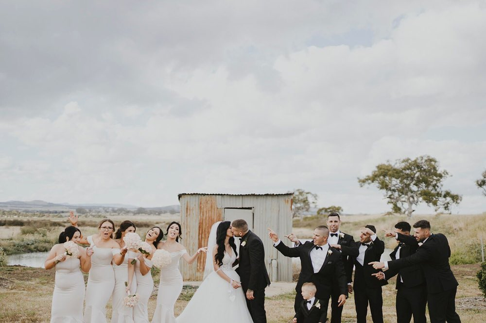 A couple is kissing with bridesmaids and groomsmen on their sides