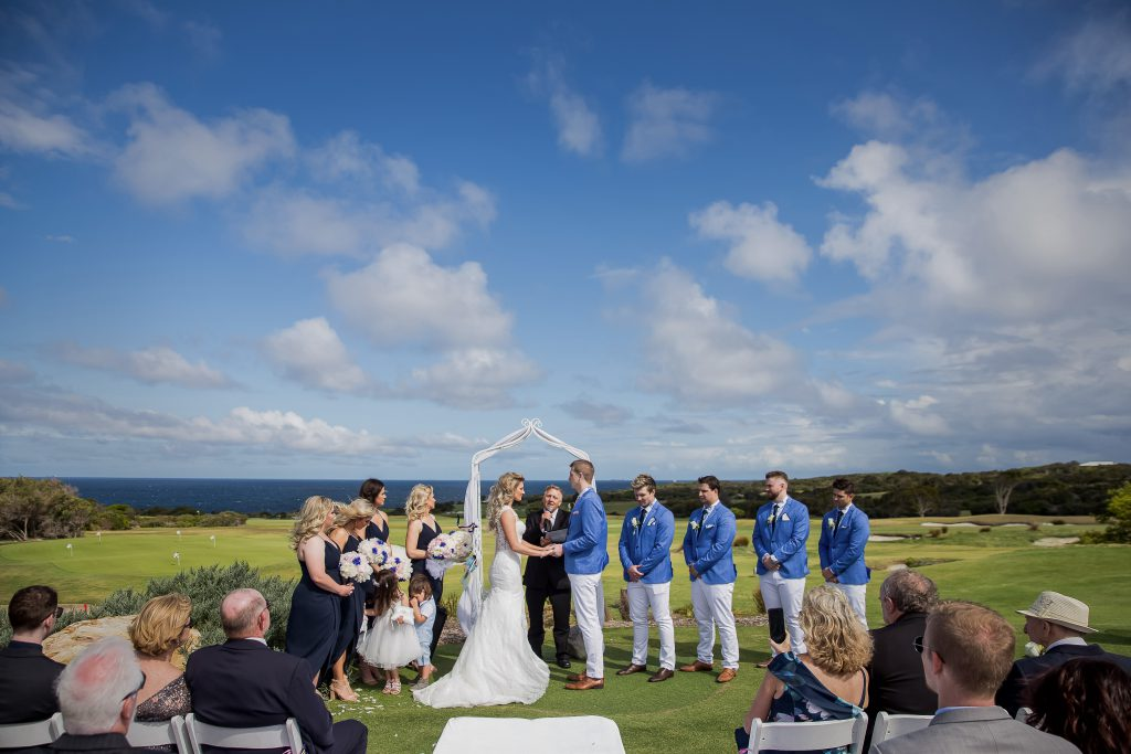 Exchanging wedding vows on a courtyard with ocean as a backdrop