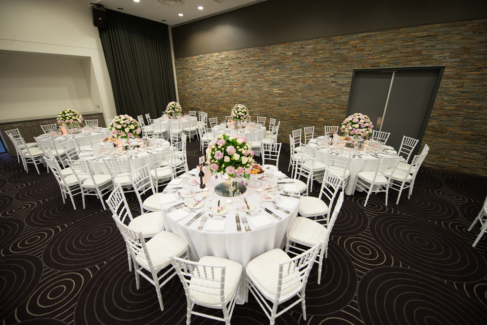 A wedding reception with six round tables on the frame and flowers on each table