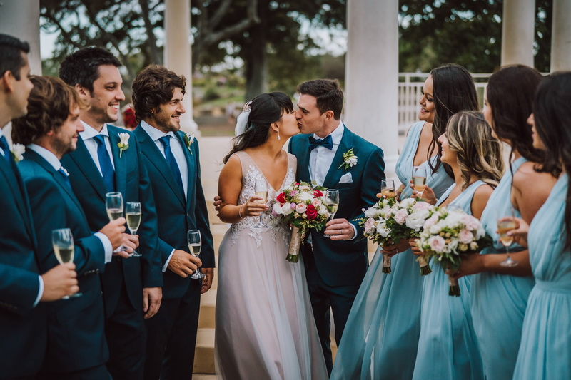 A wedding couple is kissing surrounded by bridesmaids and groomsmen