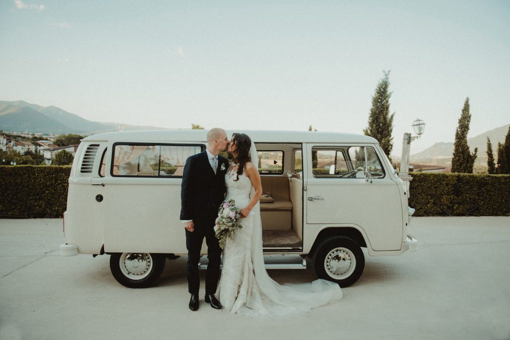 A wedding couple kissing in front of a van